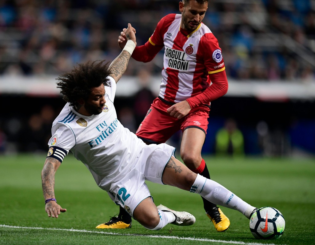 Girona's Uruguayan forward Cristhian Stuani (R) vies with Real Madrid's Brazilian defender Marcelo during the Spanish League football match between Real Madrid CF and Girona FC at the Santiago Bernabeu stadium in Madrid on March 18, 2018. / AFP PHOTO / JAVIER SORIANO (Photo credit should read JAVIER SORIANO/AFP/Getty Images)