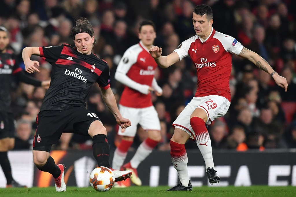 AC Milan's Italian midfielder Riccardo Montolivo (L) vies with Arsenal's Swiss midfielder Granit Xhaka during the UEFA Europa League round of 16 second-leg football match between Arsenal and AC Milan at the Emirates Stadium in London on March 15, 2018. / AFP PHOTO / Ben STANSALL (Photo credit should read BEN STANSALL/AFP/Getty Images)