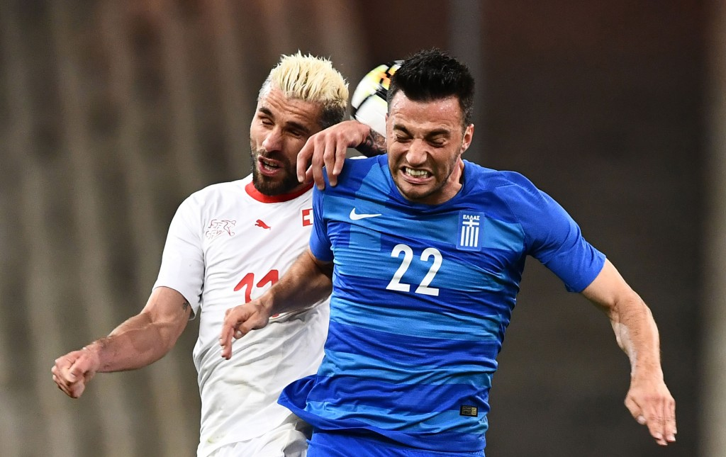 Greece's Andreas Samaris (R) fights for the ball with Switzerland's Valon Behrami during the international friendly football match between Greece and Switzerland in Athens on March 23, 2018. (Photo courtesy - Aris Messinis/AFP/Getty Images)