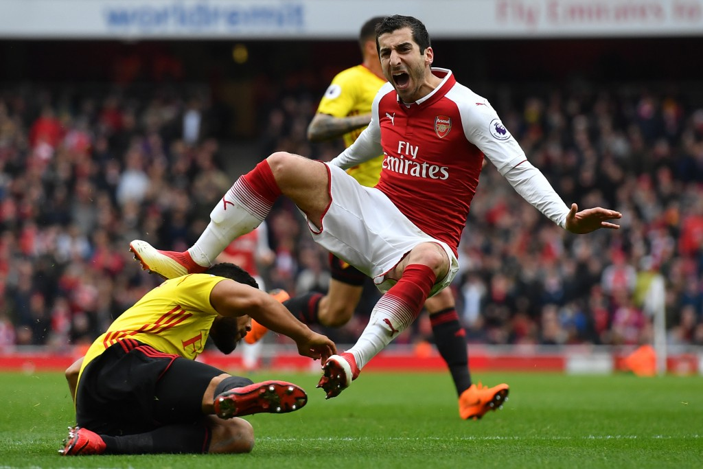 TOPSHOT - Arsenal's Armenian midfielder Henrikh Mkhitaryan reacts to a challenge from Watford's English-born Jamaican defender Adrian Mariappa (L) during the English Premier League football match between Arsenal and Watford at the Emirates Stadium in London on March 11, 2018. / AFP PHOTO / Ben STANSALL / RESTRICTED TO EDITORIAL USE. No use with unauthorized audio, video, data, fixture lists, club/league logos or 'live' services. Online in-match use limited to 75 images, no video emulation. No use in betting, games or single club/league/player publications. / (Photo credit should read BEN STANSALL/AFP/Getty Images)