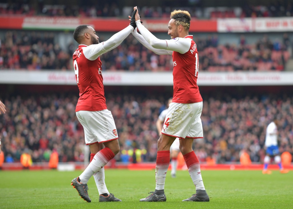 Arsenal's Gabonese striker Pierre-Emerick Aubameyang (R) celebrates scoring the team's second goal with Arsenal's French striker Alexandre Lacazette during the English Premier League football match between Arsenal and Stoke City at the Emirates Stadium in London on April 1, 2018. / AFP PHOTO / Oliver GREENWOOD / RESTRICTED TO EDITORIAL USE. No use with unauthorized audio, video, data, fixture lists, club/league logos or 'live' services. Online in-match use limited to 75 images, no video emulation. No use in betting, games or single club/league/player publications. / (Photo credit should read OLIVER GREENWOOD/AFP/Getty Images)