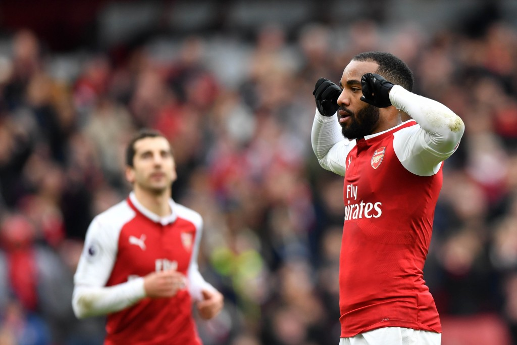 Arsenal's French striker Alexandre Lacazette (R) celebrates scoring the team's third goal during the English Premier League football match between Arsenal and Stoke City at the Emirates Stadium in London on April 1, 2018. / AFP PHOTO / Oliver GREENWOOD / RESTRICTED TO EDITORIAL USE. No use with unauthorized audio, video, data, fixture lists, club/league logos or 'live' services. Online in-match use limited to 75 images, no video emulation. No use in betting, games or single club/league/player publications. / (Photo credit should read OLIVER GREENWOOD/AFP/Getty Images)