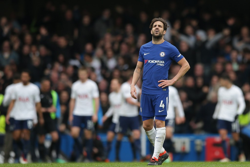 Chelsea's Spanish midfielder Cesc Fabregas reacts as Tottenham players celebrate after scoring their third goal during the English Premier League football match between Chelsea and Tottenham Hotspur at Stamford Bridge in London on April 1, 2018. / AFP PHOTO / Daniel LEAL-OLIVAS / RESTRICTED TO EDITORIAL USE. No use with unauthorized audio, video, data, fixture lists, club/league logos or 'live' services. Online in-match use limited to 75 images, no video emulation. No use in betting, games or single club/league/player publications. / (Photo credit should read DANIEL LEAL-OLIVAS/AFP/Getty Images)