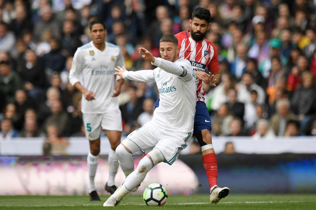 Real Madrid's Spanish defender Sergio Ramos challenges Atletico Madrid's Spanish forward Diego Costa (back R) during the Spanish league football match between Real Madrid CF and Club Atletico de Madrid at the Santiago Bernabeu stadium in Madrid on April 8, 2018. / AFP PHOTO / GABRIEL BOUYS (Photo credit should read GABRIEL BOUYS/AFP/Getty Images)