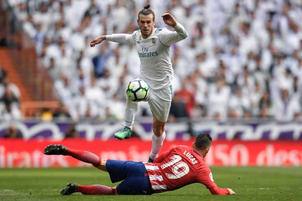 TOPSHOT - Real Madrid's Welsh forward Gareth Bale jumps over Atletico Madrid's French defender Lucas Hernandez (bottom) during the Spanish league football match between Real Madrid CF and Club Atletico de Madrid at the Santiago Bernabeu stadium in Madrid on April 8, 2018. / AFP PHOTO / GABRIEL BOUYS (Photo credit should read GABRIEL BOUYS/AFP/Getty Images)