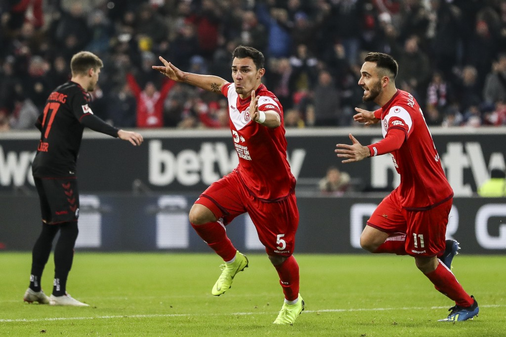 DUESSELDORF, GERMANY - DECEMBER 15: Kaan Ayhan #5 of Fortuna Dusseldorf celebrates with teammate Kenan Karaman after scoring his team's first goal during the Bundesliga match between Fortuna Duesseldorf and Sport-Club Freiburg at Esprit-Arena on December 15, 2018 in Duesseldorf, Germany. (Photo by Maja Hitij/Bongarts/Getty Images)