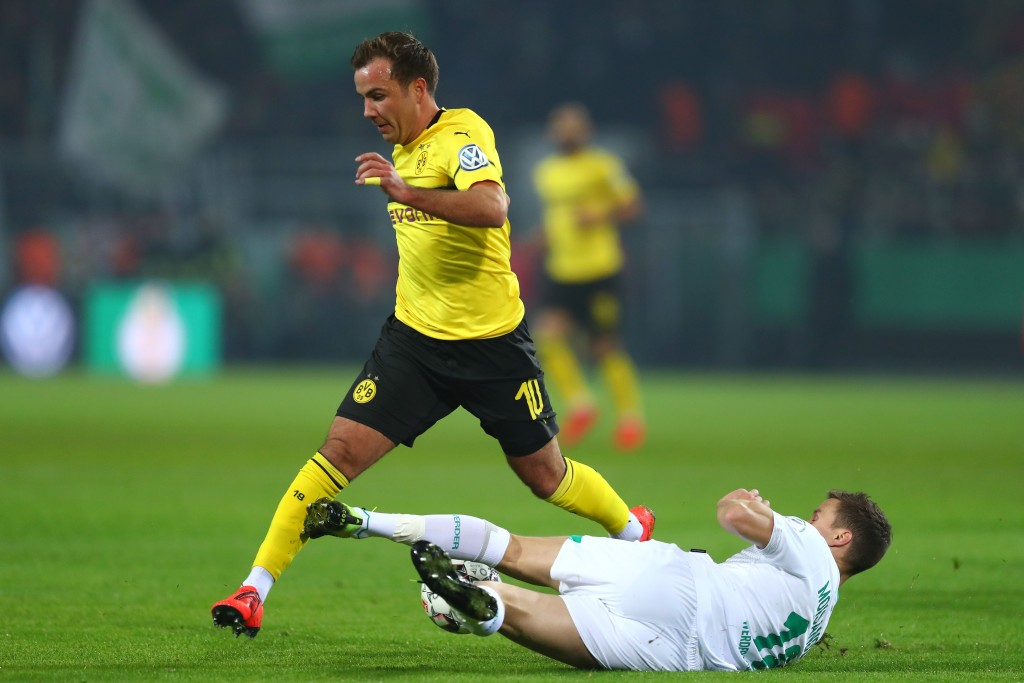 DORTMUND, GERMANY - FEBRUARY 05: Niklas Moisander of Werder Bremen tackles Mario Gotze of Borussia Dortmund during the DFB Cup match between Borussia Dortmund and Werder Bremen at Signal Iduna Park on February 5, 2019 in Dortmund, Germany. (Photo by Lars Baron/Bongarts/Getty Images)