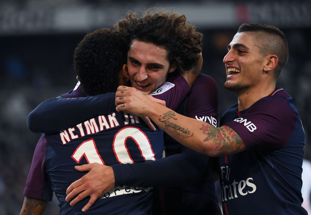 Paris Saint-Germain's Brazilian forward Neymar (L) celebrates with Paris Saint-Germain's French midfielder Adrien Rabiot (C) and Paris Saint-Germain's Italian midfielder Marco Verratti (R) after scoring a goal during the French L1 football match between Marseille (OM) and Paris Saint-Germain (PSG) on October 22, 2017, at the Velodrome Stadium in Marseille, southeastern France. / AFP PHOTO / ANNE-CHRISTINE POUJOULAT (Photo credit should read ANNE-CHRISTINE POUJOULAT/AFP/Getty Images)