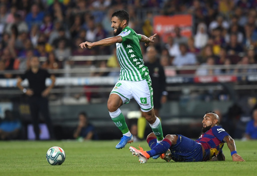 BARCELONA, SPAIN - AUGUST 25: Nabil Fekir of Real Betis is challenged by Arturo Vidal of Barcelona during the Liga match between FC Barcelona and Real Betis at Camp Nou on August 25, 2019 in Barcelona, Spain. (Photo by Alex Caparros/Getty Images)