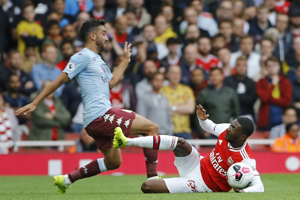 Maitland-Niles makes the tackle that earned him the red-card and let Arsenal down. (Photo by Tolga Akmen/AFP/Getty Images)
