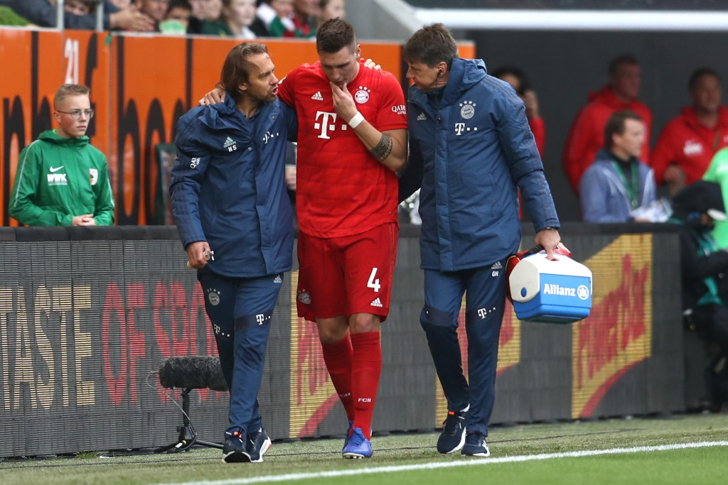 AUGSBURG, GERMANY - OCTOBER 19: Niklas Suele of FC Bayern Munich receives medical treatment during the Bundesliga match between FC Augsburg and FC Bayern Muenchen at WWK-Arena on October 19, 2019 in Augsburg, Germany. (Photo by Alexander Hassenstein/Bongarts/Getty Images)
