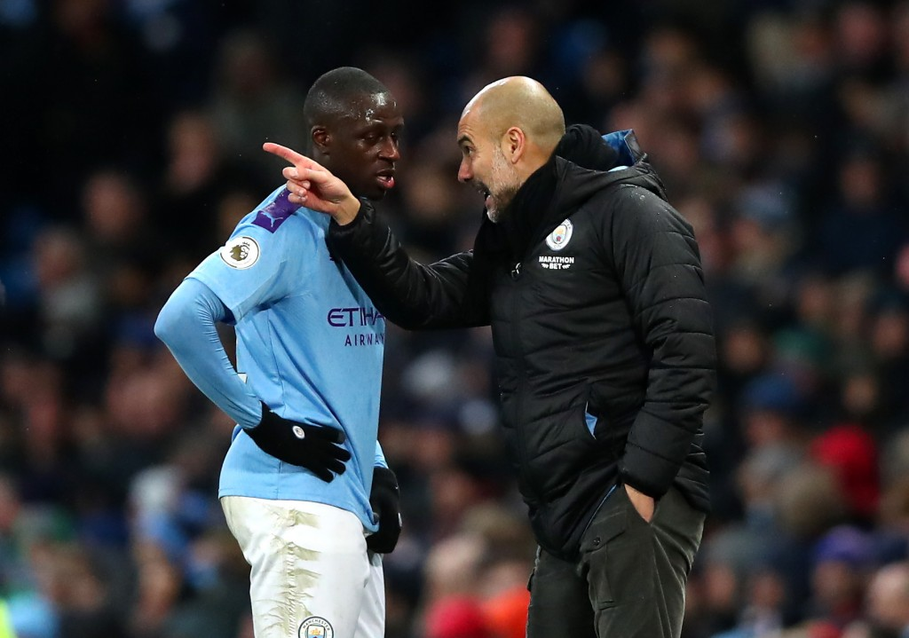 MANCHESTER, ENGLAND - DECEMBER 21: Pep Guardiola, Manager of Manchester City talks to Benjamin Mendy of Manchester City during the Premier League match between Manchester City and Leicester City at Etihad Stadium on December 21, 2019 in Manchester, United Kingdom. (Photo by Clive Brunskill/Getty Images)