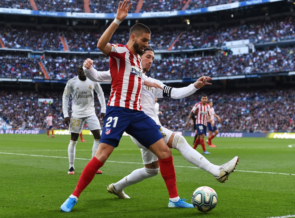 MADRID, SPAIN - FEBRUARY 01: Yannick Carrasco of Atletico Madrid is challenged by Sergio Ramos of Real Madrid during the La Liga match between Real Madrid CF and Club Atletico de Madrid at Estadio Santiago Bernabeu on February 01, 2020 in Madrid, Spain. (Photo by Denis Doyle/Getty Images)